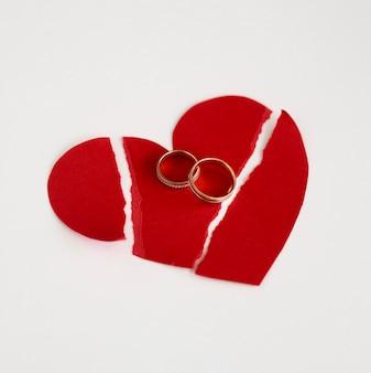 Anelli di matrimonio e cuore di carta spezzato