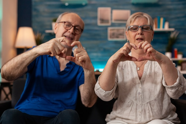 Married aged couple doing heart symbol with hands