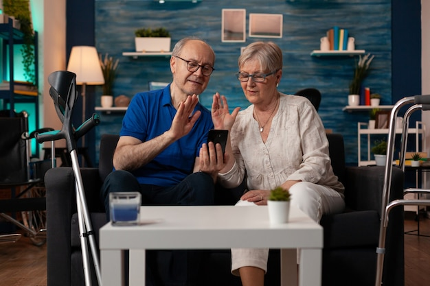 Married aged couple using smartphone for video call