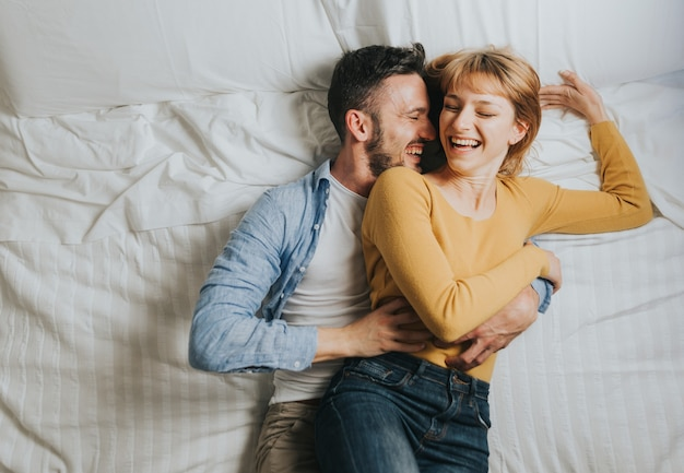 Married coupe in love laughing having fun playing on the bed.