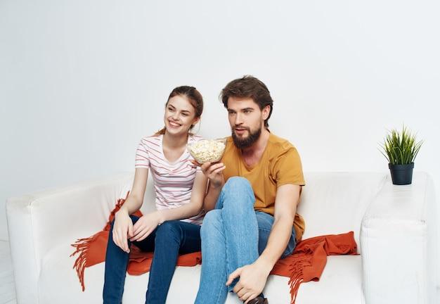 自宅の夫婦がソファで休むポップコーンの楽しみ
