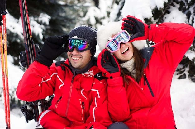 Married couple in bright jackets preparing to ski together in the winter forest
