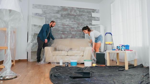家の装飾のためのプラスチックシートでソファを覆う夫婦。リフォームと改善中のアパートの改装と住宅建設。修理と装飾。