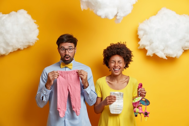 Married couple expect for child. husband and wife pose with baby stuff, afro american pregnant woman laughs happily, holds diaper and mobile, shocked future father poses with newborn clothes