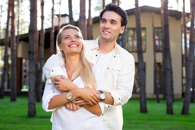 夫婦。彼女を抱きしめながら彼の美しい妻の後ろに立っているハンサムな素敵な男