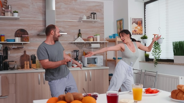 Married couple having fun dancing in kitchen during breakfast. carefree husband and wife laughing, singing, dancing listening musing, living happy and worry free. positive people.