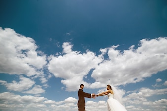 Married couple holding hands with clouds in the sky