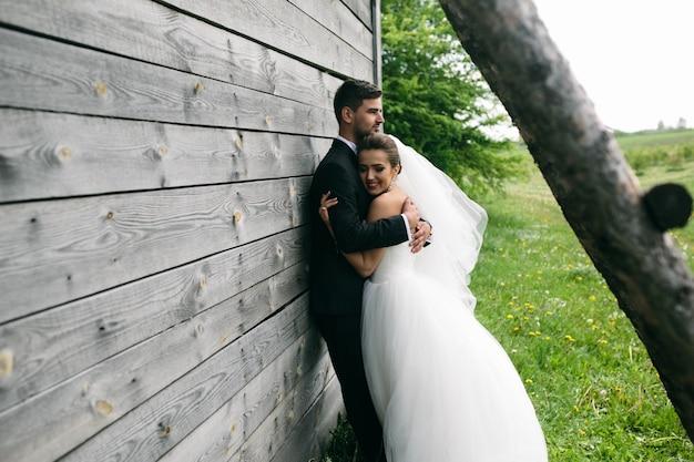 Супружеская пара обниматься рядом с деревянной хижине