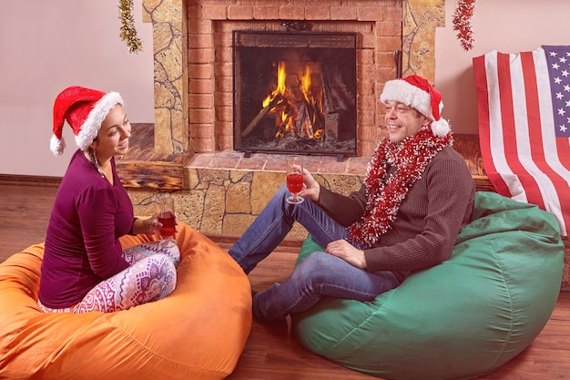 Married couple husband and wife celebrating christmas sitting beside  fireplace on frameless furniture bean bags or bag chairs.