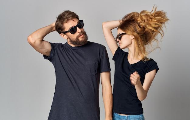 Супружеская пара в черной футболке солнцезащитные очки позирует на изолированном фоне