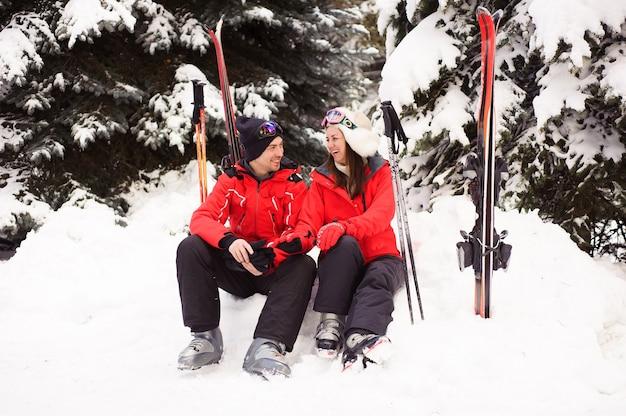 冬の森で一緒にスキーをする準備をしている明るいジャケットを着た夫婦。