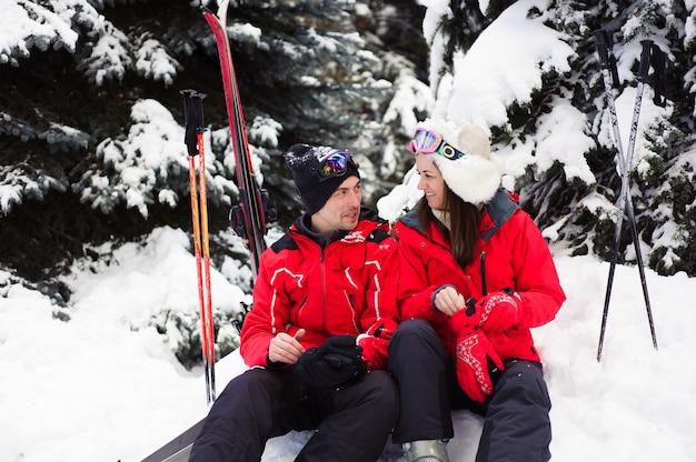 Супружеская пара в ярких куртках готовится вместе кататься на лыжах в зимнем лесу.