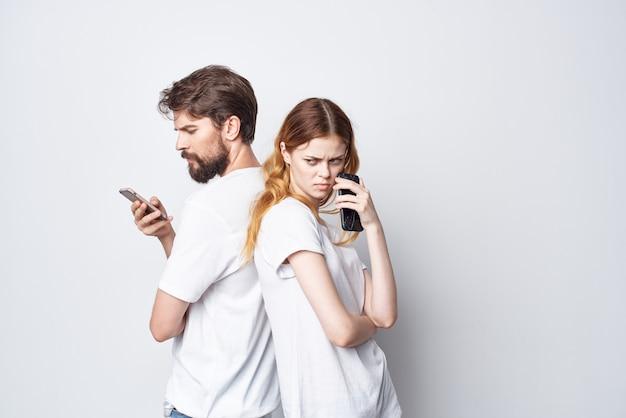 Супружеская пара в белых футболках с телефонами в руках изолированный фон