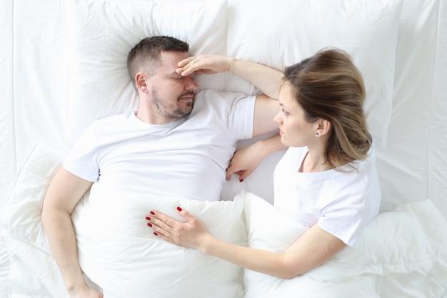 Супружеская пара лежит в постели сверху. мужчина держит голову