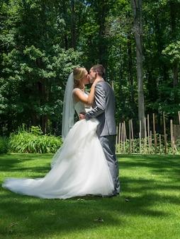 結婚されていたカップルが日光の下で緑に囲まれた庭でキス