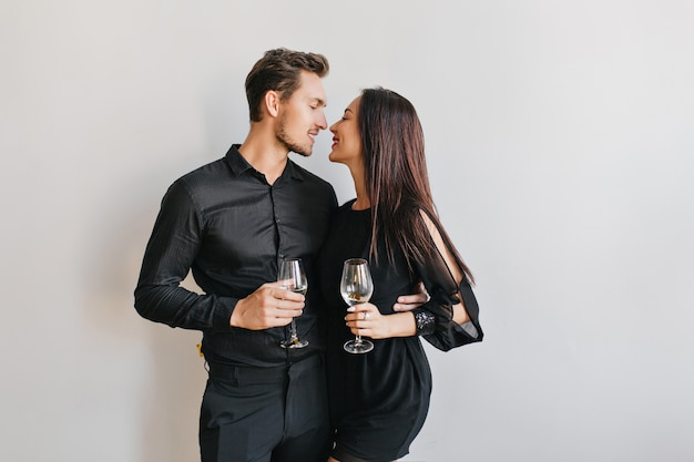 Married couple kissing at party, holding glasses of champagne in hands