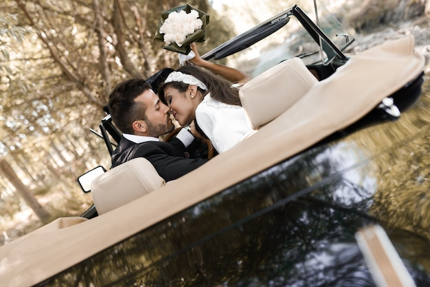 Married couple kissing in wedding car