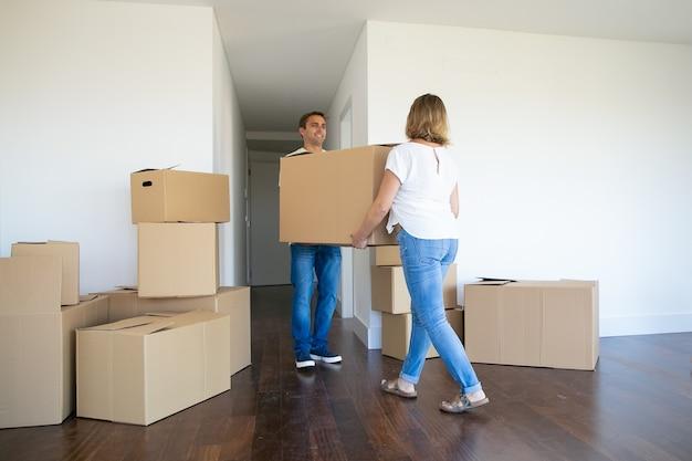 Супружеская пара выходит из квартиры, неся мультяшную коробку к входу вместе