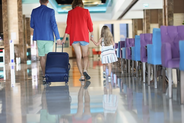 Married couple and little daughter walking with suitcase in hotel lobby back view. family travel abroad with children concept