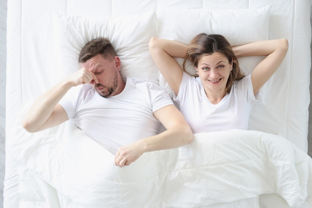 Married couple lying in bed. man covering his nose with his hand