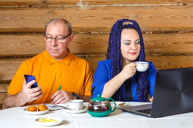 A married couple a man in glasses and a woman with blue afro braids at the table a woman drinks tea and works at a computer listens to a man. horizontal photo