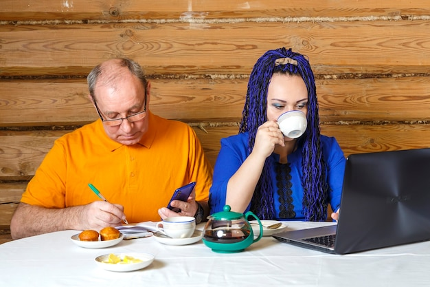 A married couple man in glasses and a woman with blue afro braids at the table work at the computer together. horizontal photo