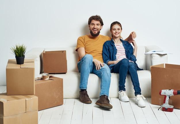 Супружеская пара перемещает коробки с вещами, распаковывая интерьер