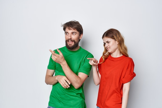 Married couple multicolored tshirts communication quarrel light background