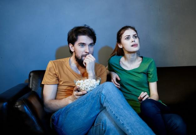 Супружеская пара на диване смотрит телевизор
