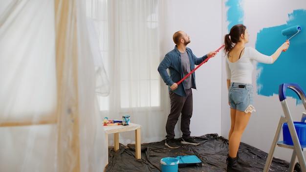 Супружеская пара красит стену квартиры валиком во время ремонта дома синей краской. отделка, цвет, ремонт, отделка.