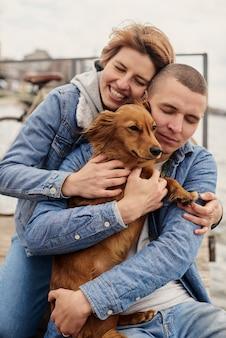 ペットと一緒に桟橋で休んでいる夫婦。
