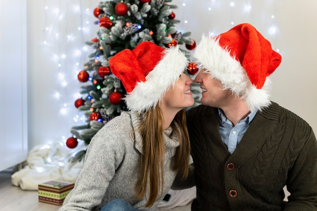 A married couple in santa claus hats kiss each other.