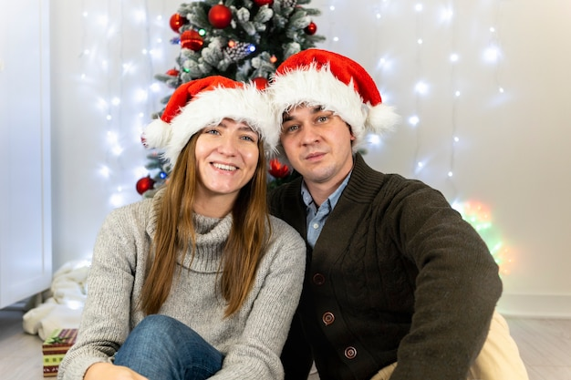 Married couple in santa claus hats.
