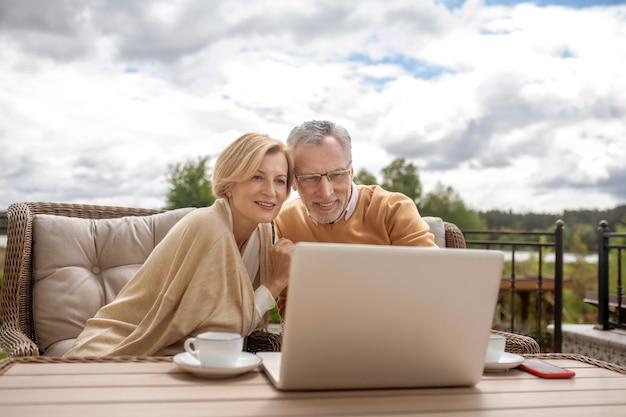함께 인터넷 서핑을 하는 테이블에 앉아 있는 부부