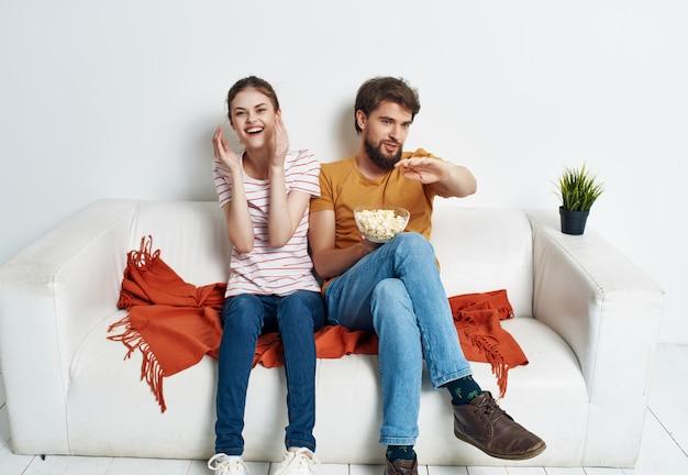 Супружеская пара, сидя на диване дома, смотрит фильм