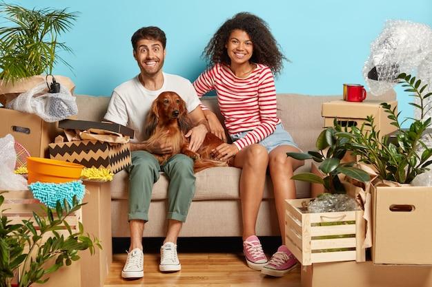 Coppia sposata sul divano con il cane circondato da scatole di cartone