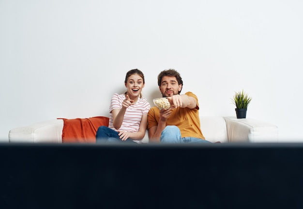 Супружеская пара смотрит телевизор на диване