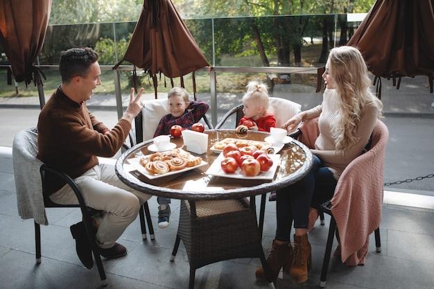 Семейная пара с детьми, дочерью и сыном за столиком в кафе. счастливая традиционная пара, семейное счастье.