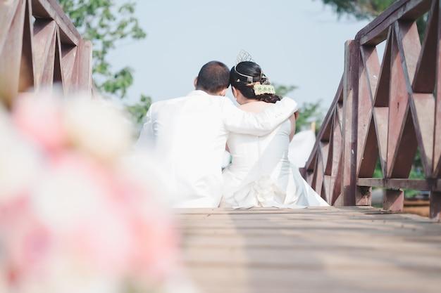 夫婦は、ロマンチックな愛の概念である木製の橋でお互いを抱きしめるために一緒に座っています。