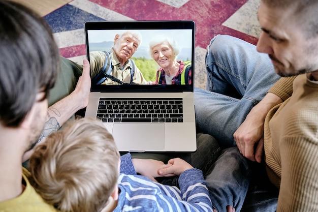 Семейная гей-пара со своим сыном по видеосвязи с дедушкой и дедушкой сидит на диване дома