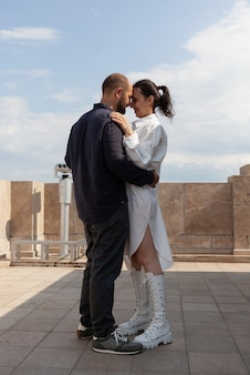 Coppia felice sposata che si abbraccia sulla terrazza della torre celebrando la relazione