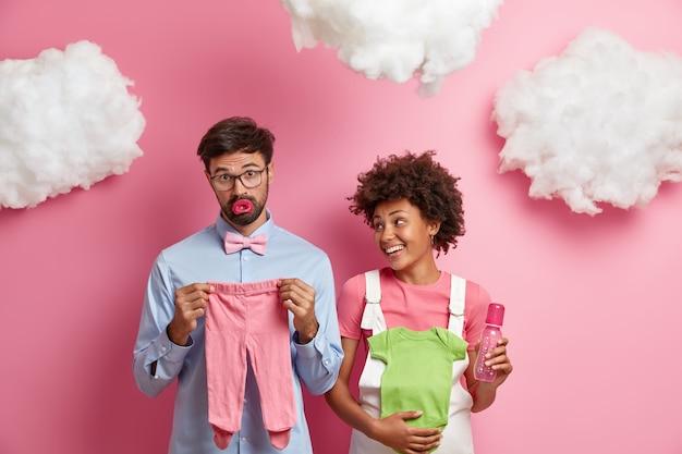 結婚した混血カップルは赤ちゃんを期待し、新生児に必要なアイテムを購入します。元気な妊婦さんがボディスーツと哺乳瓶を持って乳児用に、夫を喜んで見ています。幸せな期待の概念