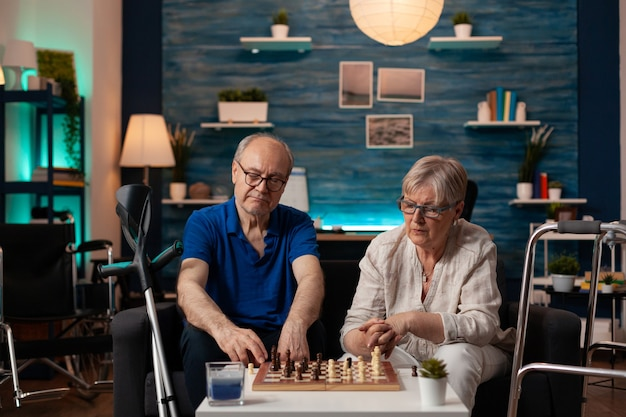 Married old couple playing chess game on table at home