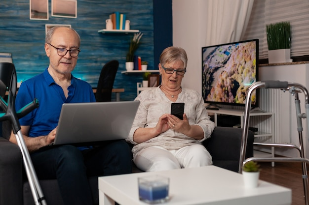 Married people enjoying retirement with technology at home