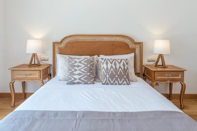 モダンな装飾が施された寝室の結婚した木製ベッド。