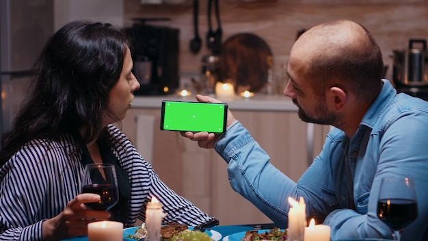 Married young couple holding mockup phone at dinner. happy looking at green screen template chroma key isolated smart phone display using techology internet sitting at the table in kitchen.