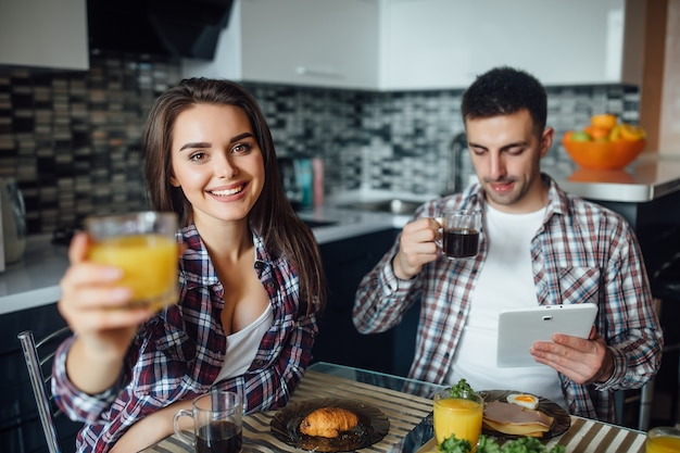 Marriede couple of man and woman have a breakfast together in morning at kitchen, loooking recipes in internet on laptop