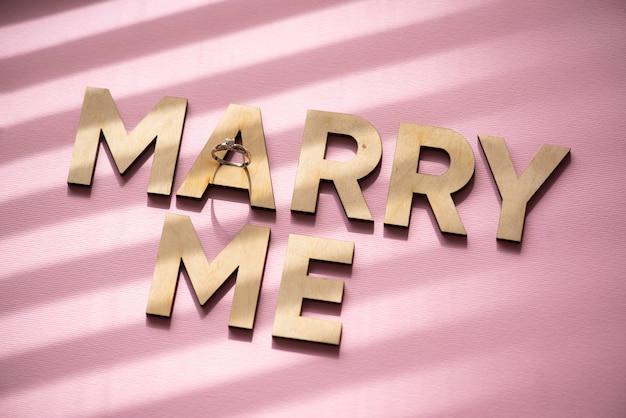 ピンクの表面に木製の文字と結婚してください