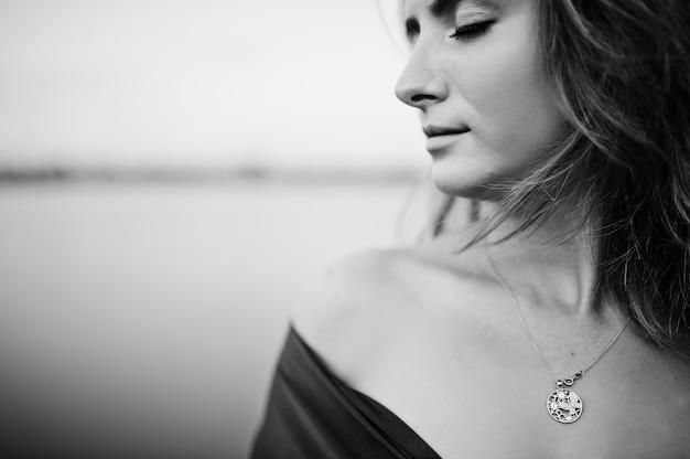 Закройте вверх по портрету белокурой чувственной женщины в красном платье marsala представляя против озера.