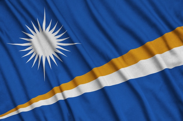 Marshall islands flag is depicted on a sports cloth fabric with many folds.